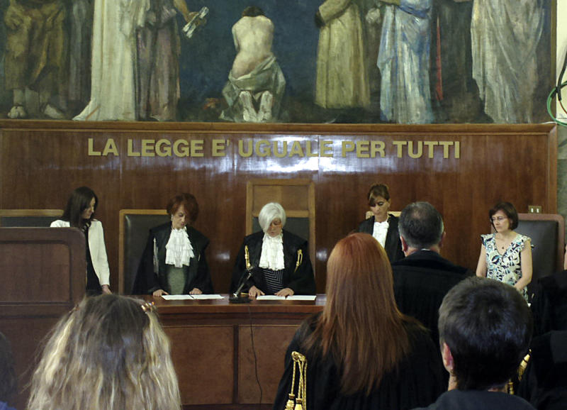 """In this photo taken with a cellular phone, judge Anna Maria Gatto, center, reads the sentence at the Milan court, Italy, Friday, July 19, 2013. A Milan court on Friday, July 19, 2013 convicted three of ex-premier Silvio Berlusconi's former aides of procuring prostitutes for the media mogul's infamous """"bunga bunga"""" parties. The court also handed down stiff prison terms: seven years to Emilio Fede, a longtime executive in the mogul's TV networks; seven years to Dario """"Lele"""" Mora, a talent agent, and five years to Nicole Minetti, a former regional politician who professed love for the ex-premier. Berlusconi wasn't on trial in this case, but he was convicted separately last month of paying for sex with a minor and trying to cover it up. Both he and the young woman, a Moroccan who goes by her stage name """"Ruby,"""" had denied having sex. (AP Photo/Antonio Calanni)"""
