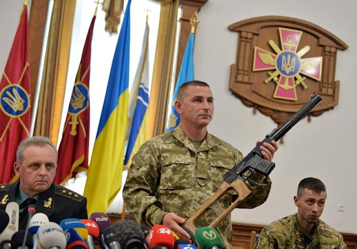 A Ukrainian officer shows a special nine-millimetre calibre rifle, seized from captured Russian servicemen, during a press conference in Kiev on May 18, 2015 (AFP Photo/Genya Savilov)