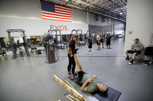 In this Oct. 8, 2018, photo, Kurt DiGiacomo, right, lifts his leg as he works with Cienna Collins during a range of motion evaluation at Exos in Carlsbad, Calif. DiGiacomo played football for the San Diego Chargers and Kansas City Chiefs in the NFL. (AP Photo/Gregory Bull)