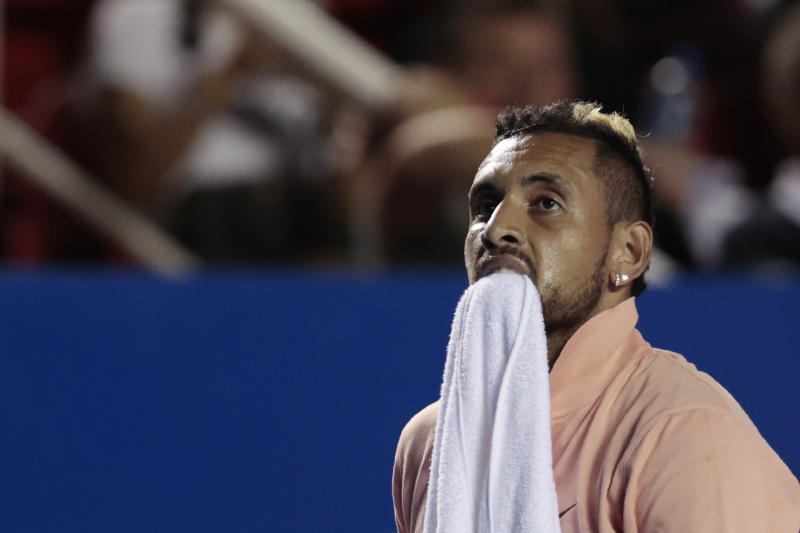 Australia's Nick Kyrgios carries a towel between his teeth during an opening-round match against France's Ugo Humbert at the Mexican Open tennis tournament in Acapulco, Mexico, Tuesday, Feb. 25, 2020. Kyrgios retired from the match following the first set. (AP Photo/Rebecca Blackwell)