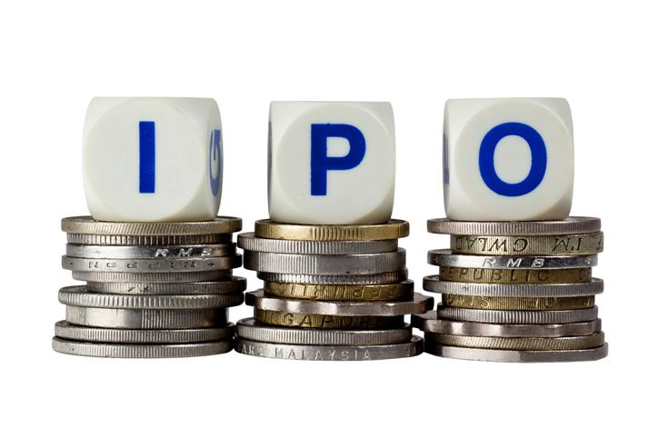 Three white blocks with letters IPO on them sitting atop small stacks of coins.
