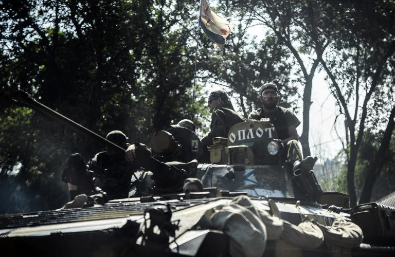 Pro-Russia militants sit on a tank as they drive towards the front line on the outskirts of Donetsk, on July 27, 2014