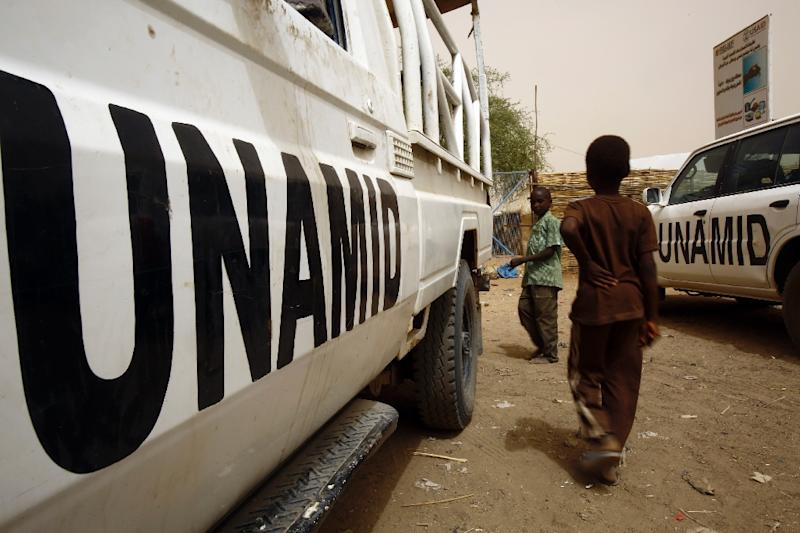 Sudanese children walk past a UN-African Union Mission in Darfur vehicle on April 12, 2016