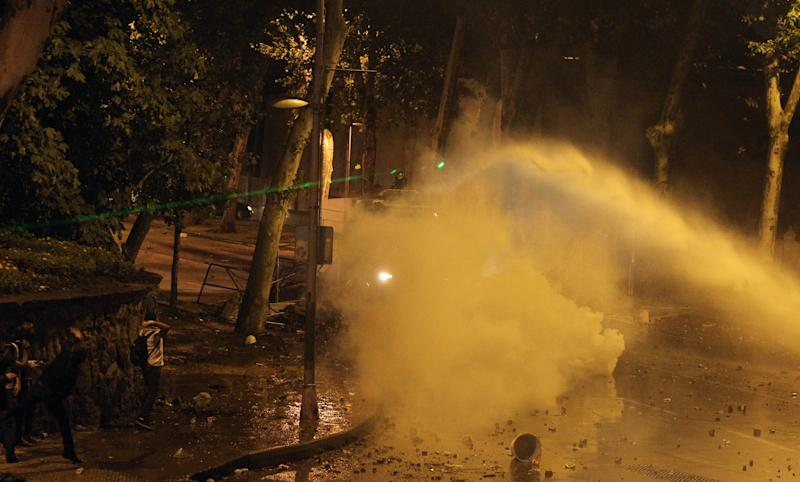 Police use a water cannon and tear gas as protesters light the area with a green laser light during the third day of nationwide anti-government protest near the Prime Minister's office at Besiktas area in Istanbul, late Sunday, June 2, 2013. Protests in Istanbul and several other Turkish cities appear to have subsided, after days of fierce clashes following a police crackdown on a peaceful gathering. The demonstrations grew out of anger over a violent police crackdown of a peaceful environmental protest at Istanbul's Taksim Square and spread to other Turkish cities. (AP Photo/Thanassis Stavrakis)