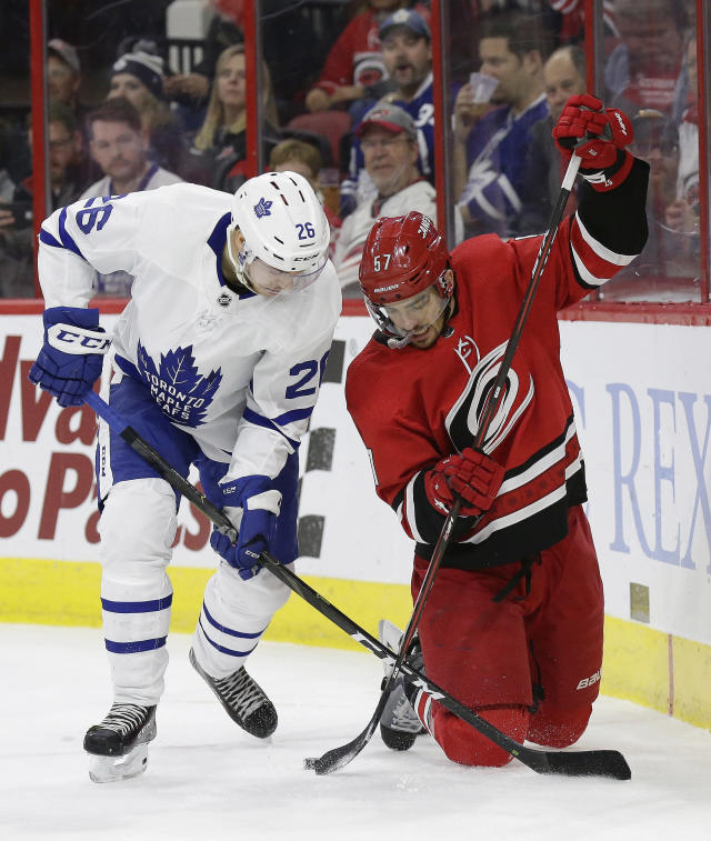 Toronto Maple Leafs' Par Lindholm (26), of Sweden, and Carolina Hurricanes' Trevor van Riemsdyk (57) chase the puck during the first period of an NHL hockey game in Raleigh, N.C., Wednesday, Nov. 21, 2018. (AP Photo/Gerry Broome)