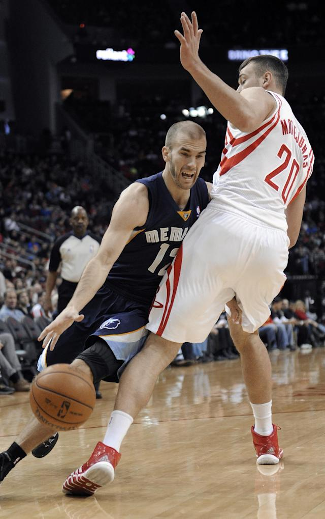 Memphis Grizzlies' Nick Calathes (12) drives the ball around Houston Rockets' Donatas Motiejunas (20) during the first half of an NBA basketball game Friday, Jan. 24, 2014, in Houston. (AP Photo/Pat Sullivan)