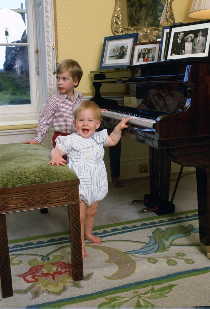 <p>Harry, 11 months, plays with the piano with his brother William, 3, at their home in Kensington Palace.</p>