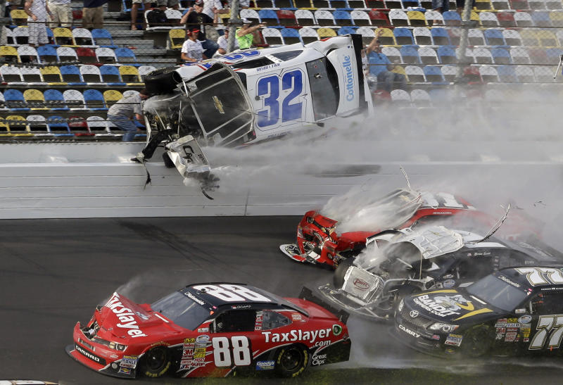 Kyle Larson (32) goes airborne and into the catch fence in a multi-car crash involving Dale Earnhardt Jr. (88), Parker Kligerman (77), Justin Allgaier (31) and Brian Scott (2) during the final lap of the NASCAR Nationwide Series auto race at Daytona International Speedway, Saturday, Feb. 23, 2013, in Daytona Beach, Fla. (AP Photo/John Raoux)