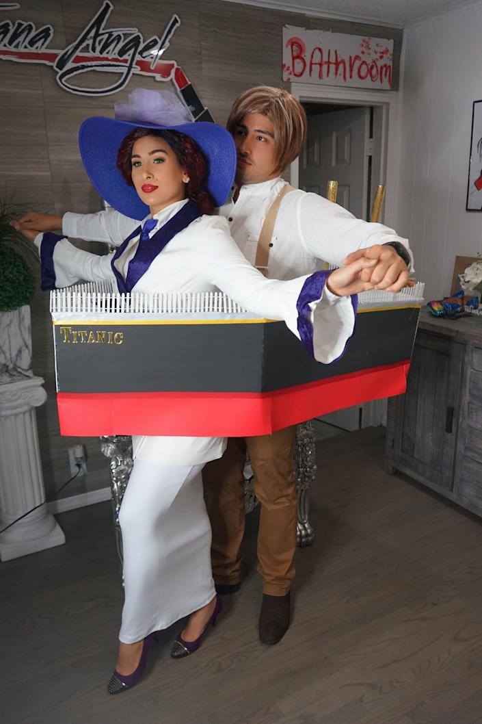 """A couple dressed as Jack and Rose from """"Titanic"""" pose inside of a cardboard boat."""
