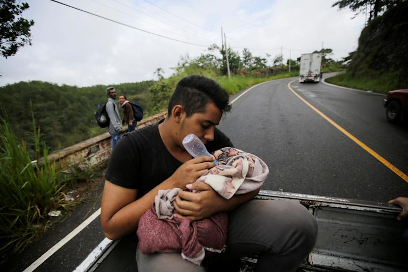 A man feeds his child in the back of a truck.