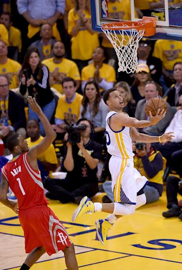 OAKLAND, CA - MAY 19: Stephen Curry #30 of the Golden State Warriors attempts a reverse layup over Trevor Ariza #1 of the Houston Rockets during the second half in Game One of the Western Conference Finals of the NBA Playoffs at ORACLE Arena on May 19, 2015 in Oakland, California. NOTE TO USER: User expressly acknowledges and agrees that, by downloading and or using this photograph, User is consenting to the terms and conditions of the Getty Images License Agreement. (Photo by Thearon W. Henderson/Getty Images)