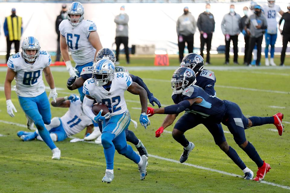 Running back D'Andre Swift (32) of the Detroit Lions rushes for a touchdown over cornerback Malcolm Butler (21) of the Tennessee Titans in the fourth quarter of the game at Nissan Stadium on Dec. 20, 2020, in Nashville, Tennessee.