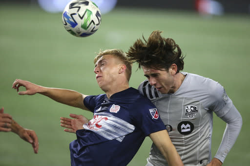 New England Revolution forward Adam Buksa, left and Montreal Impact forward Bojan Krkic, right vie for a head ball during the first half of an MLS soccer match Friday, Nov. 20, 2020, in Foxborough, Mass. (AP Photo/Stew Milne)
