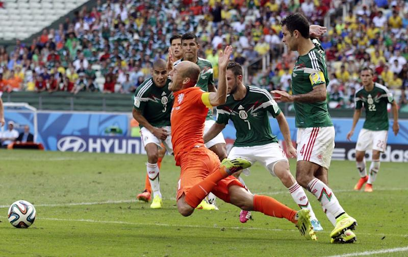 Netherlands' Arjen Robben, center, goes down to win a penalty during the World Cup round of 16 soccer match between the Netherlands and Mexico at the Arena Castelao in Fortaleza, Brazil, Sunday, June 29, 2014. Netherlands won the match 2-1