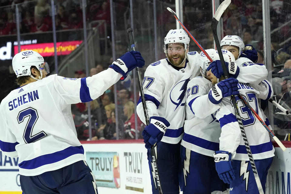 Tampa Bay Lightning defenseman Luke Schenn (2) congratulates center Barclay Goodrow, right, along with defenseman Victor Hedman (77), center Yanni Gourde (37) and center Blake Coleman (20) following Goodrow's goal during the third period in Game 1 of an NHL hockey Stanley Cup second-round playoff series against the Carolina Hurricanes in Raleigh, N.C., Sunday, May 30, 2021. (AP Photo/Gerry Broome)