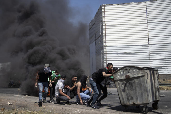 Palestinian demonstrators take cover during clashes with Israeli forces at the Hawara checkpoint, south of the West Bank city of Nablus, Friday, May 14, 2021. Health officials say several Palestinians were killed by Israeli army fire, at protests that took place in several locations across the West Bank of Friday. (AP Photo/Majdi Mohammed)