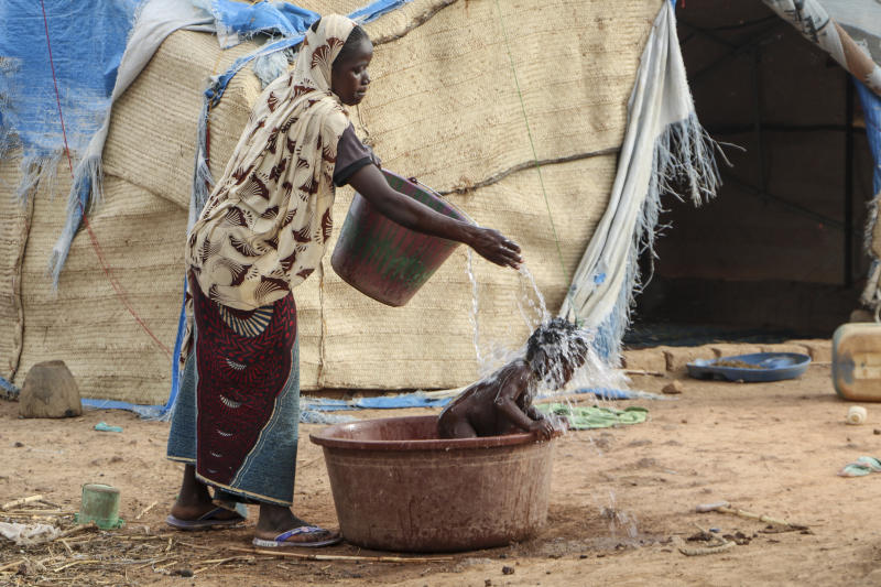 In this Thursday, May 14, 2020, photo, a mother who fled the north after her village was attacked by gunmen, washes her baby outside the tent in Nouna, Burkina Faso, where she now lives and depends on food handouts. Violence linked to Islamic extremists has spread to Burkina Faso's breadbasket region, pushing thousands of people toward hunger and threatening to cut off food aid for millions more. (AP Photo/Sam Mednick)