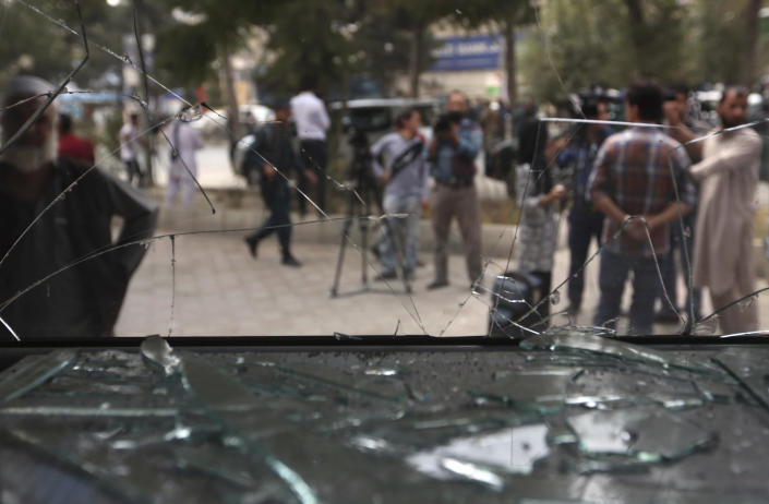 <p>Afghan journalists stand in front of the broken glass of shop at the site of a suicide bombing in Kabul, Afghanistan, Tuesday, Aug. 29, 2017. (Photo: Rahmat Gul/AP) </p>