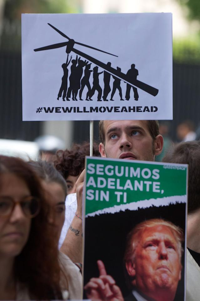 <p>Greenpeace protesters stand in silence with banners outside the U.S. embassy in Madrid, Spain, Friday, June 2, 2017. The protesters gathered at the gates of the United States embassy in the Spanish capital to protest President Donald Trump's decision to pull the world's second-largest carbon dioxide emitter out of the Paris climate agreement. (AP Photo/Paul White) </p>