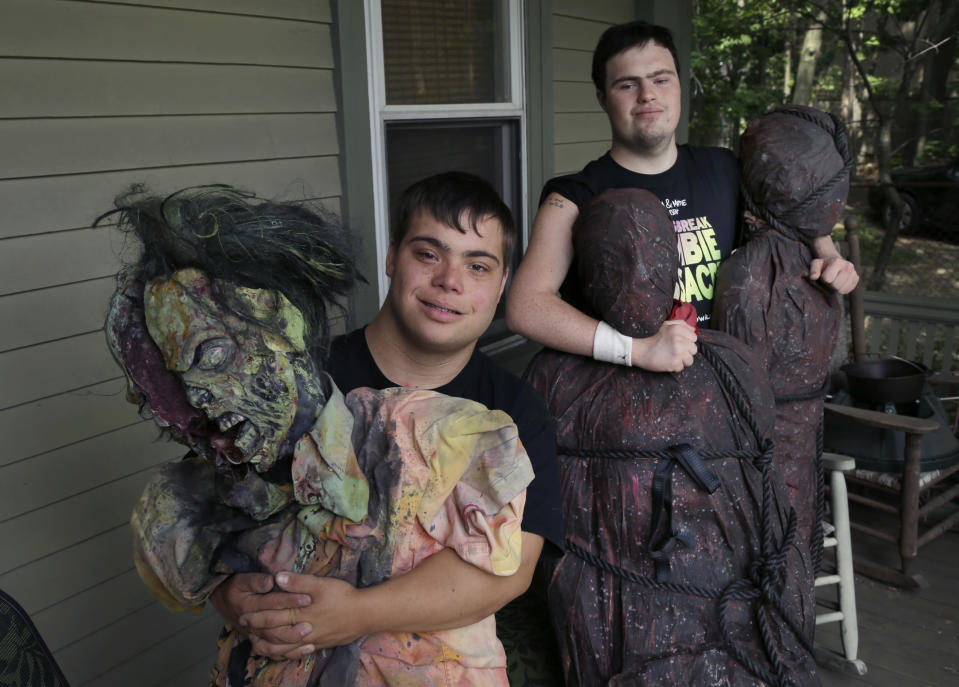 """FILE — In this July 12, 2016, file photo, Sam Suchmann, right, and Mattie Zufelt pose with ghoulish figures at Sam's home in Providence, R.I. The two young men with Down syndrome who caused a sensation four years ago when they created their own gory zombie movie are back, this time in a documentary championed by a Hollywood luminary that chronicles their tenacious, years-long effort to see their silver screen dream come to fruition. """"Sam & Mattie Make a Zombie Movie,"""" was released Tuesday, April 6, 2021, on Apple TV. (AP Photo/Elise Amendola, File)"""