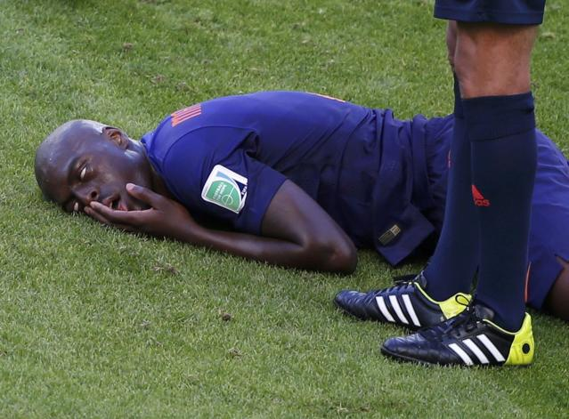 Bruno Martins Indi of the Netherlands lies injured on the pitch after being fouled by Australia's Tim Cahill during their 2014 World Cup Group B soccer match at the Beira Rio stadium in Porto Alegre June 18, 2014. REUTERS/Marko Djurica (BRAZIL - Tags: SOCCER SPORT WORLD CUP TPX IMAGES OF THE DAY TOPCUP)