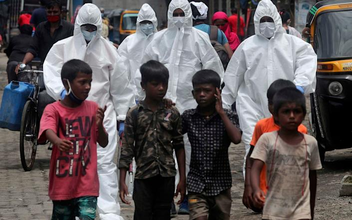 Health workers arrive to screen people at a slum in Mumbai, India - AP