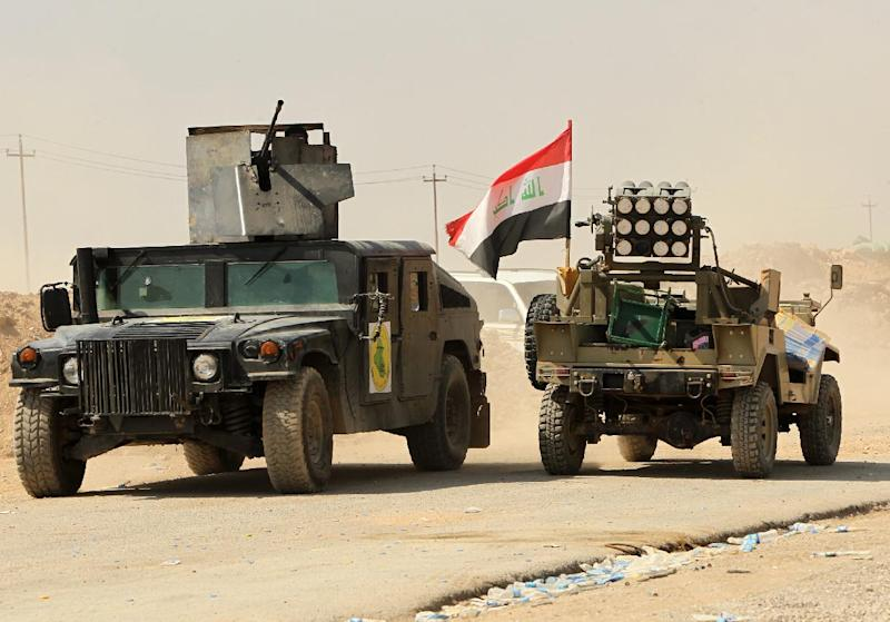 Vehicles belonging to fighters from the Iraqi Imam Ali Brigade are positioned during heavy clashes with Islamic State militants in Tuz Khurmatu in Salaheddin province on September 1, 2014 (AFP Photo/Ali al-Saadi)
