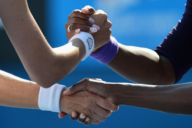MELBOURNE, AUSTRALIA - JANUARY 20: Venus Williams and Serena Williams of the United States of America are congratulated by Nadia Petrova of Russia and Katarina Srebotnik Slovenia after winning their third round doubles match during day seven of the 2013 Australian Open at Melbourne Park on January 20, 2013 in Melbourne, Australia. (Photo by Vince Caligiuri/Getty Images)