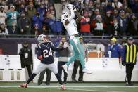 Miami Dolphins wide receiver DeVante Parker catches a pass over New England Patriots cornerback Stephon Gilmore in the second half of an NFL football game, Sunday, Dec. 29, 2019, in Foxborough, Mass. (AP Photo/Elise Amendola)