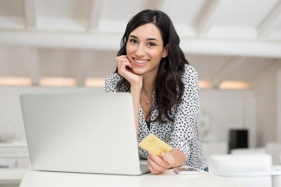 A smiling young woman holding a credit card in her left hand while in front of her laptop.