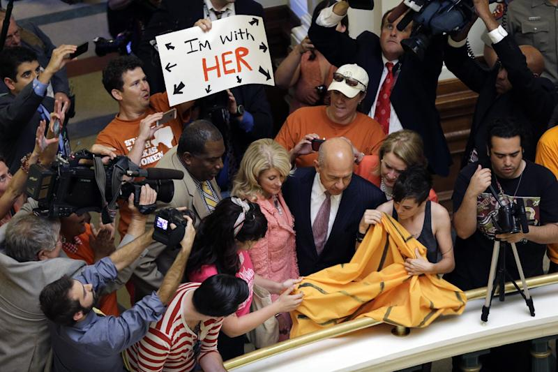 Sen. Royce West, D-Dallas, left, Sen. Wendy Davis, D-Fort Worth, center, and Sen. John Whitmire, D-Houston, right, walk into the Capitol rotunda as the Texas Senate takes a break from their debate an abortion bill, Friday, July 12, 2013, in Austin, Texas. The bill would require doctors to have admitting privileges at nearby hospitals, only allow abortions in surgical centers, dictate when abortion pills are taken and ban abortions after 20 weeks. (AP Photo/Eric Gay)