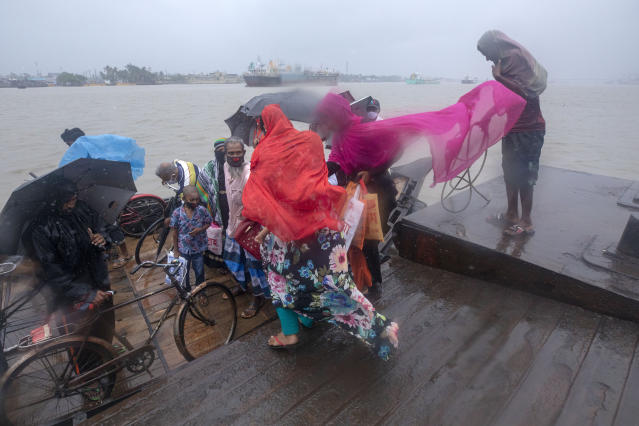 """DAKOP, KHULNA, BANGLADESH - 2020/05/20: Man and women cross the river immediately before Cyclone Amphan hits Bangladesh costal area in Khulna. Authorities have scrambled to evacuate low lying areas in the path of Amphan, which is only the second """"super cyclone"""" to form in the northeastern Indian Ocean since records began. (Photo by K M Asad/LightRocket via Getty Images)"""