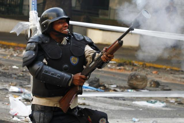 A riot policeman shoots tear gas at anti-government protesters during a protest in Caracas March 8, 2014. Latin American foreign ministers will meet next week to discuss the unrest in Venezuela that has left at least 20 dead and convulsed the South American OPEC nation, diplomatic sources said on Friday. REUTERS/Carlos Garcia Rawlins (VENEZUELA - Tags: POLITICS CIVIL UNREST)