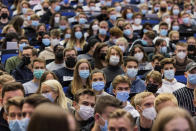 """Students wear mouth-to-nose coverings while sitting close to each other during the lecture """"BWL 1"""" in lecture hall H1 of the Westfaelische Wilhelms-Universitaet in Muenster, Germany, Monday, Oct. 11, 2021. For the first time since the beginning of the Corona pandemic, lectures in the winter semester 21/22 have started in presence under 3G conditions. (Rolf Vennenbernd/dpa via AP)"""