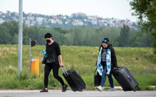 Women walk with their luggage while crossing the Bratislava-Berg border