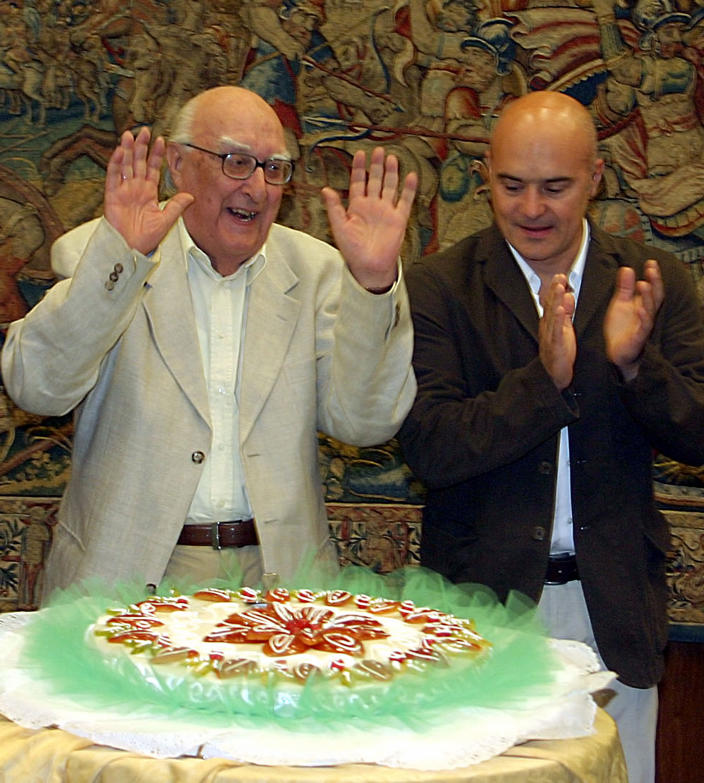 FILE - In this Sept. 14, 2005 file photo, Italian author Andrea Camilleri, left, flanked by actor Luca Zingaretti, celebrates his 80th birthday, at the RAI headquarters, in Rome. Camilleri, known for his popular novels and TV series centered on the much-loved inspector Salvo Montalbano, died in Rome, Wednesday, July 17, 2019, at age 93. Camilleri was Italy's most successful writer, but until he was nearly 70 he had been a virtually unknown author of a handful of historical novels set in his native Sicily. (AP Photo/Sandro Pace, file)