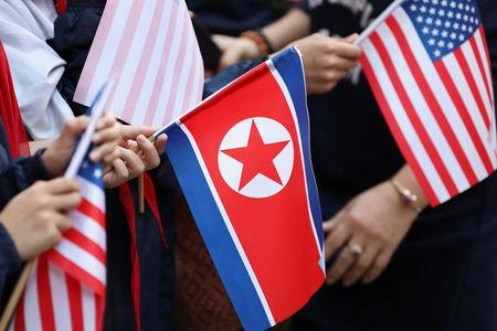 Bystanders holding North Korea and U.S. flags wait for the motorcade of U.S. President Donald Trump in Hanoi
