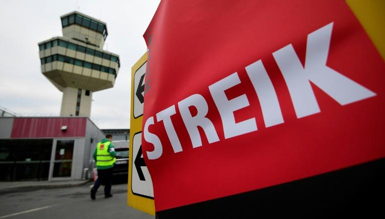 "An information sign covered with a banner reading ""Strike"" during a wage strike of ground staff at Berlin's Tegel airport on March 10, 2017"