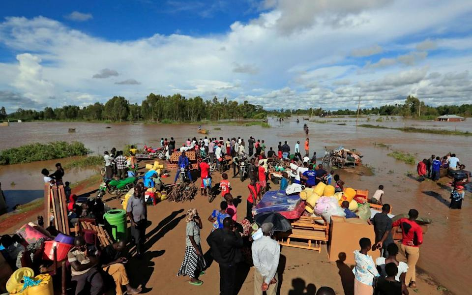 Residents gather on the safe grounds with their belongings after the River Nzoia burst its banks in Busia County, Kenya.
