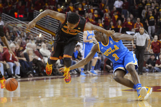 Southern California guard Brendyn Taylor, left, and UCLA guard Jordan Adams dive for a loose ball during the first half of an NCAA college basketball game, Saturday, Feb. 8, 2014, in Los Angeles. (AP Photo/Mark J. Terrill)