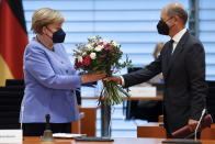 German Finance Minister Olaf Scholz hands a bouquet of flowers to German Chancellor Angela Merkel on occasion of her birthday on July 17, as they arrive for the weekly German cabinet meeting at the Chancellery in Berlin, Germany, Wednesday, July 21, 2021. (Axel Schmidt/Pool Photo via AP)