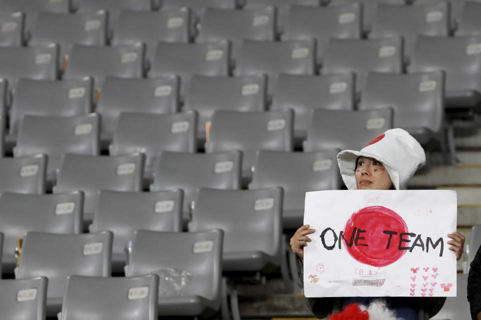 FILE - In this Oct. 20, 2019, file photo, a Japan fan reacts after the Rugby World Cup quarterfinal loss to South Africa at Tokyo Stadium in Tokyo, Japan. The start of the Japanese Top League season will be pushed back until next month after 62 players and staff from six teams tested positive for the coronavirus, the Japan Rugby Football Union said Thursday, Jan. 14, 2021. (AP Photo/Eugene Hoshiko, File)