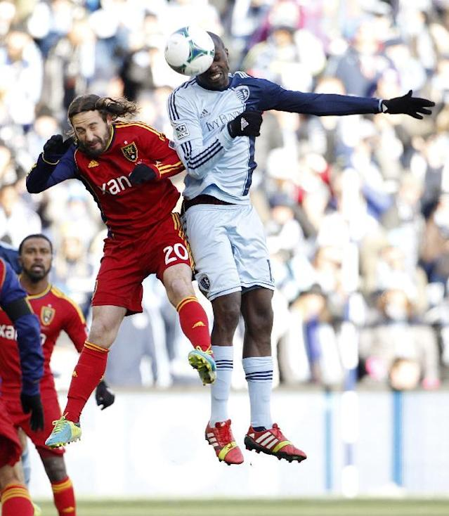 Sporting Kansas City defender Lawrence Olum (13) heads the ball as Real Salt Lake midfielder Ned Grabavoy (20) defends during the first half of the MLS Cup final soccer match in Kansas City, Kan., Saturday, Dec. 7, 2013. (AP Photo/Colin E. Braley)