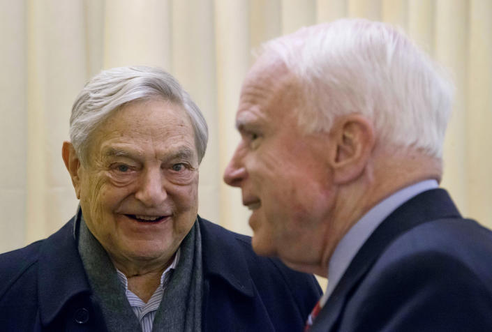 FILE - In this Thursday, Jan. 23, 2014 file photo, Chairman of Soros Fund Management George Soros, left, talks with U.S. Sen. John McCain, R-Ariz., during the World Economic Forum in Davos, Switzerland. The mail bomb that showed up in the mail box of billionaire investor and philanthropist George Soros on Oct. 22, 2018 is a reminder of his place as one of the far right's most hated boogeymen. (AP Photo/Michel Euler)