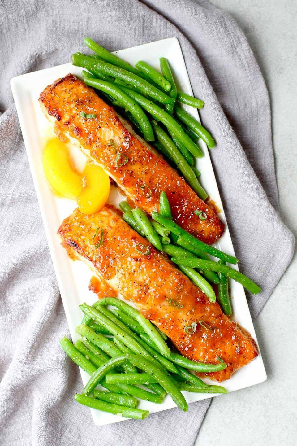 """<p>This light, fast salmon dinner for two goes from weeknight-worthy to """"<em>wow</em> what's in that?"""" thanks to a deliciously sweet peach glaze.</p><p><strong>Get the recipe at <a href=""""https://marisamoore.com/bourbon-peach-glazed-salmon-date-night-dinner/"""" rel=""""nofollow noopener"""" target=""""_blank"""" data-ylk=""""slk:Marisa Moore"""" class=""""link rapid-noclick-resp"""">Marisa Moore</a>.</strong></p>"""