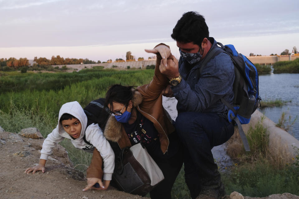 A migrant family from Brazil seeking asylum struggles up an embankment to reach the United States after crossing the dammed Colorado River from Mexico in Yuma, Ariz., in June.