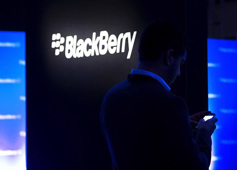 FILE - In this Wednesday, Jan. 30, 2013, file photo, a man uses his Blackberry as people wait for the Blackberry BB10 launch in Toronto. Fairfax Financial Holdings has offered to buy BlackBerry in a deal that values the Canadian smartphone company at about US$4.7 billion, on Monday, Sept. 23, 2013. (AP Photo/The Canadian Press, Nathan Denette, File)