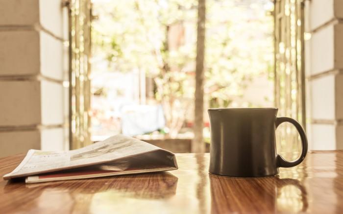 Close-up of a cup of coffee and a newspaper on a wood cafe table overlooking a leafy street.