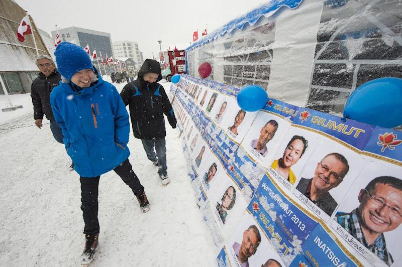 Youths walk past placards depicting candidates for the general election, in Nuuk, Greenland, Tuesday, March 12, 2013. Greenlanders are voting to elect the semi-autonomous nation's 31-seat Parliament amid a strategic debate over how to handle potentially vast underground mineral wealth. (AP Photo/Polfoto, Leiff Josefsen) DENMARK OUT