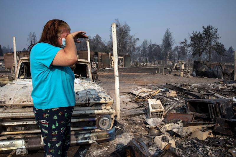 Heather Marshall stands amid what remains of her home at Coleman Creek Estates mobile home park in Phoenix, Oregon, on Thursday. The area was destroyed when a wildfire swept through on Tuesday. The Marshalls had lived at the park for 21 years. (Photo: Paula Bronstein/ASSOCIATED PRESS)